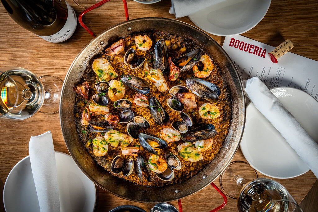 Spanish paella with saffron rice, shrimp, clams and mussels served in a shallow pan served with white wine from Boqueria Spanish restaurant and tapas bar in NYC and DC.