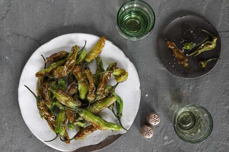 Pimientos De Padron on a white plate with cava in two clear glasses around it at the NYC & DC Spanish Restaurant, Boqueria.