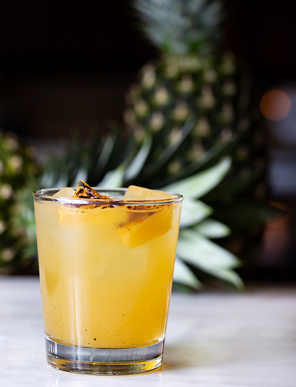 Pineapple Sangria in a glass garnished with grilled pineapple